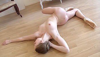 Splendid ballet dancer with a highly flexible body delightedly twisting her seductive body forming some tantalizing shapes on the floor while naked.